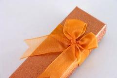 Gift box with ribbon. Closeup of orange gift box with ribbon stock image