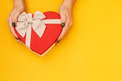 Gift box with a ribbon in female hands. The concept is suitable for love stories, birthdays and Valenti. Ne`s Day stock image