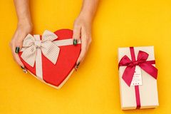 Gift box with a ribbon in female hands. The concept is suitable for love stories, birthdays and Valenti. Ne`s Day stock images
