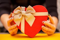 Gift box with a ribbon in female hands. The concept is suitable for love stories, birthdays and Valenti. Ne`s Day stock photography