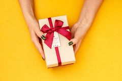 Gift box with a ribbon in female hands. The concept is suitable for love stories, birthdays and Valenti. Ne`s Day royalty free stock photo