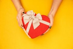 Gift box with a ribbon in female hands. The concept is suitable for love stories, birthdays and Valenti. Ne`s Day royalty free stock photos