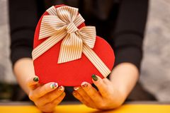 Gift box with a ribbon in female hands. The concept is suitable for love stories, birthdays and Valenti. Ne`s Day royalty free stock image