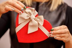 Gift box with a ribbon in female hands. The concept is suitable for love stories, birthdays and Valenti. Ne`s Day royalty free stock images