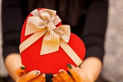 Gift box with a ribbon in female hands. The concept is suitable for love stories, birthdays and Valenti. Ne`s Day stock photo