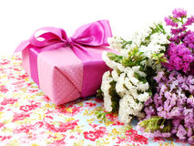 Gift box with ribbon and flower bouquet on printed fabric background Royalty Free Stock Image