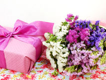 Gift box with ribbon and flower bouquet on printed fabric background Stock Photography