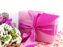 Gift box with ribbon and flower bouquet on printed fabric background Royalty Free Stock Photos