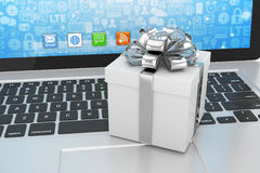 Gift box with ribbon on laptop Stock Images