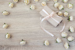 Gift box with ribbon and peach roses on wood background with empty space for text. royalty free stock photos