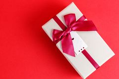 Gift box with a ribbon on a red background. The concept is suitable for love stories, birthdays and Valentine`s Day.  royalty free stock images