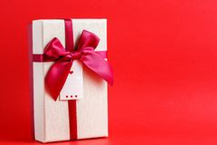 Gift box with a ribbon on a red background. The concept is suitable for love stories, birthdays and Valentine`s Day.  stock photo