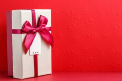 Gift box with a ribbon on a red background. The concept is suitable for love stories, birthdays and Valentine`s Day.  royalty free stock image