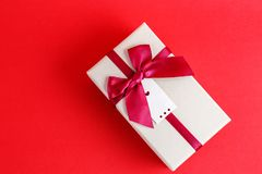 Gift box with a ribbon on a red background. The concept is suitable for love stories, birthdays and Valentine`s Day.  stock images