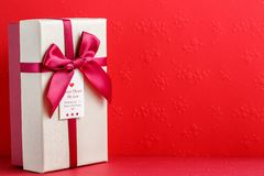 Gift box with a ribbon on a red background. The concept is suitable for love stories, birthdays and Valentine`s Day.  royalty free stock photography