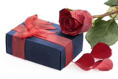 Gift box with ribbon, red rose and petals. Blue gift box with ribbon, red rose and petals on white background Stock Image