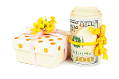 Gift box and roll of dollars. Gift box and roll of dollars over white Royalty Free Stock Photo