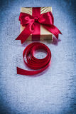 Gift box with rolled red ribbon on metallic background Stock Image