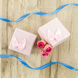 Gift box with rose flower, heart and ribbon on wooden background Royalty Free Stock Image