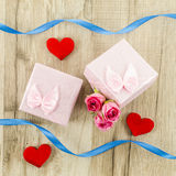 Gift box with rose flower, heart and ribbon on wooden background Stock Photo