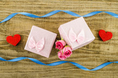 Gift box with rose flower, heart and ribbon on wooden background Stock Image
