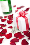 Gift box, rose petals on white background. Gift box and champagne, rose petals on a white background stock photography