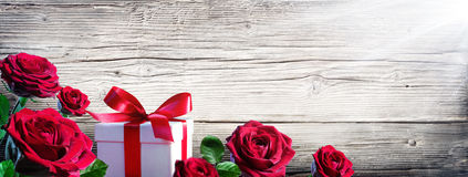 Gift Box And Roses. On Vintage Wooden Background royalty free stock image