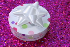 Gift Box. A round gift box with a white bow on a pink sparkling surface royalty free stock image