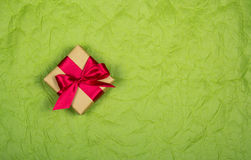 Gift box with satin bow on a pale paper background. Backgrounds and textures. Copy space. Gift box with satin bow on a pale paper background. Backgrounds and royalty free stock image