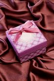 Gift box  on satin cloth Royalty Free Stock Photography