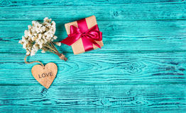 Gift box with satin ribbon, flowers and heart on a blue wooden background. Celebratory concept. Copy space Stock Photography
