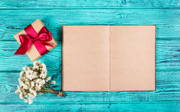 A gift box with a satin ribbon and an open book with blank pages on a blue background. Backgrounds and textures. Copy space Stock Image