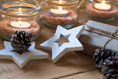 Gift box, scattered pine cone, tea lights in jars with himalaya salt, wood stars, Christmas, New Year, advent Stock Images