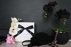 Gift box with a sexy lingerie. Flowers and present for the women. Festive underwear gift with black orchid for a lady Royalty Free Stock Photos