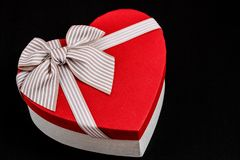 Gift box in the shape of a heart with a ribbon on a bla background. The concept is suitable for love stories, birthdays and Valent stock photo