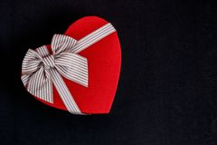Gift box in the shape of a heart with a ribbon on a bla background. The concept is suitable for love stories, birthdays and Valent royalty free stock photos