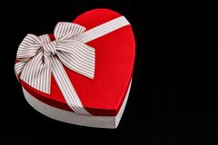 Gift box in the shape of a heart with a ribbon on a bla background. The concept is suitable for love stories, birthdays and Valent stock image