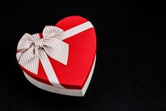 Gift box in the shape of a heart with a ribbon on a bla background. The concept is suitable for love stories, birthdays and Valent. Gift box in the shape of a royalty free stock images
