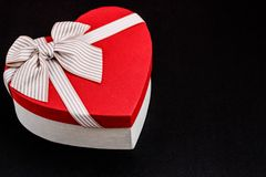 Gift box in the shape of a heart with a ribbon on a bla background. The concept is suitable for love stories, birthdays and Valent. Gift box in the shape of a stock images