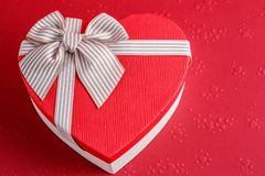 Gift box in the shape of a heart with a ribbon on a red background. The concept is suitable for love stories, birthdays and Valent. Gift box in the shape of a stock photography