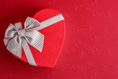 Gift box in the shape of a heart with a ribbon on a red background. The concept is suitable for love stories, birthdays and Valent. Gift box in the shape of a stock photos