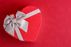 Gift box in the shape of a heart with a ribbon on a red background. The concept is suitable for love stories, birthdays and Valent. Gift box in the shape of a royalty free stock photography