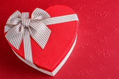 Gift box in the shape of a heart with a ribbon on a red background. The concept is suitable for love stories, birthdays and Valent royalty free stock photos