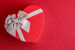 Gift box in the shape of a heart with a ribbon on a red background. The concept is suitable for love stories, birthdays and Valent. Gift box in the shape of a royalty free stock photo