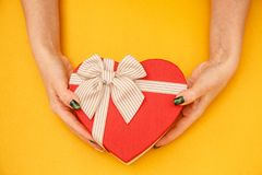 Gift box in the shape of a heart with a ribbon on in female hands. The concept is suitable for love stories, birthdays and Valenti. Ne`s Day royalty free stock photos