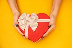 Gift box in the shape of a heart with a ribbon on in female hands. The concept is suitable for love stories, birthdays and Valenti. Ne`s Day royalty free stock images