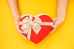 Gift box in the shape of a heart with a ribbon on in female hands. The concept is suitable for love stories, birthdays and Valenti. Ne`s Day royalty free stock photo