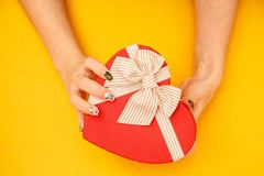 Gift box in the shape of a heart with a ribbon on in female hands. The concept is suitable for love stories, birthdays and Valenti. Ne`s Day stock images