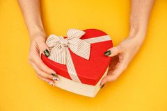 Gift box in the shape of a heart with a ribbon on in female hands. The concept is suitable for love stories, birthdays and Valenti. Ne`s Day stock photo