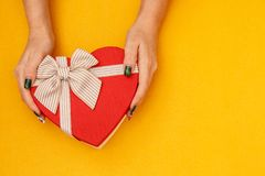 Gift box in the shape of a heart with a ribbon on in female hands. The concept is suitable for love stories, birthdays and Valenti. Ne`s Day royalty free stock photography